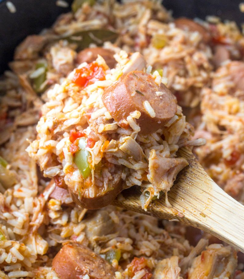 a wooden spoon scooping out the cooked chicken, sausage, and rice