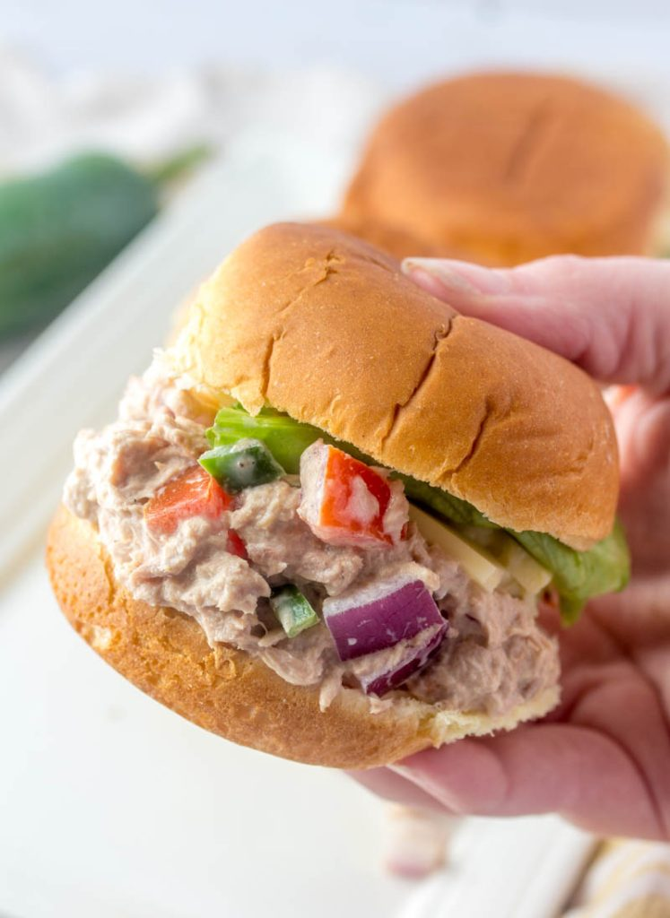 Fiesta Tuna Salad Sliders; a close up shot with one slider held up by a hand