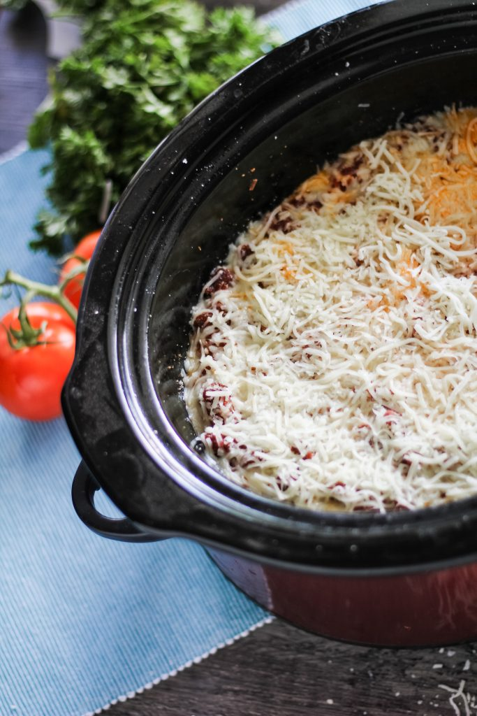 lasagna shown in the black bowl of a slow cooker