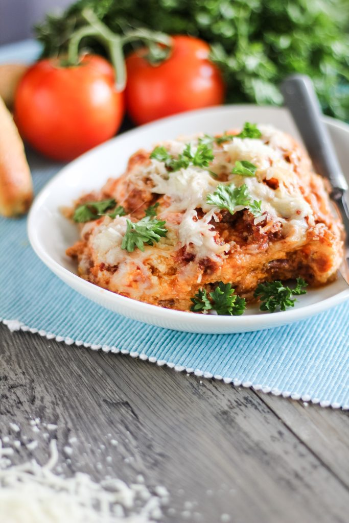 a slice of crockpot lasagna served on a white plate with fresh tomatoes and herbs in the background