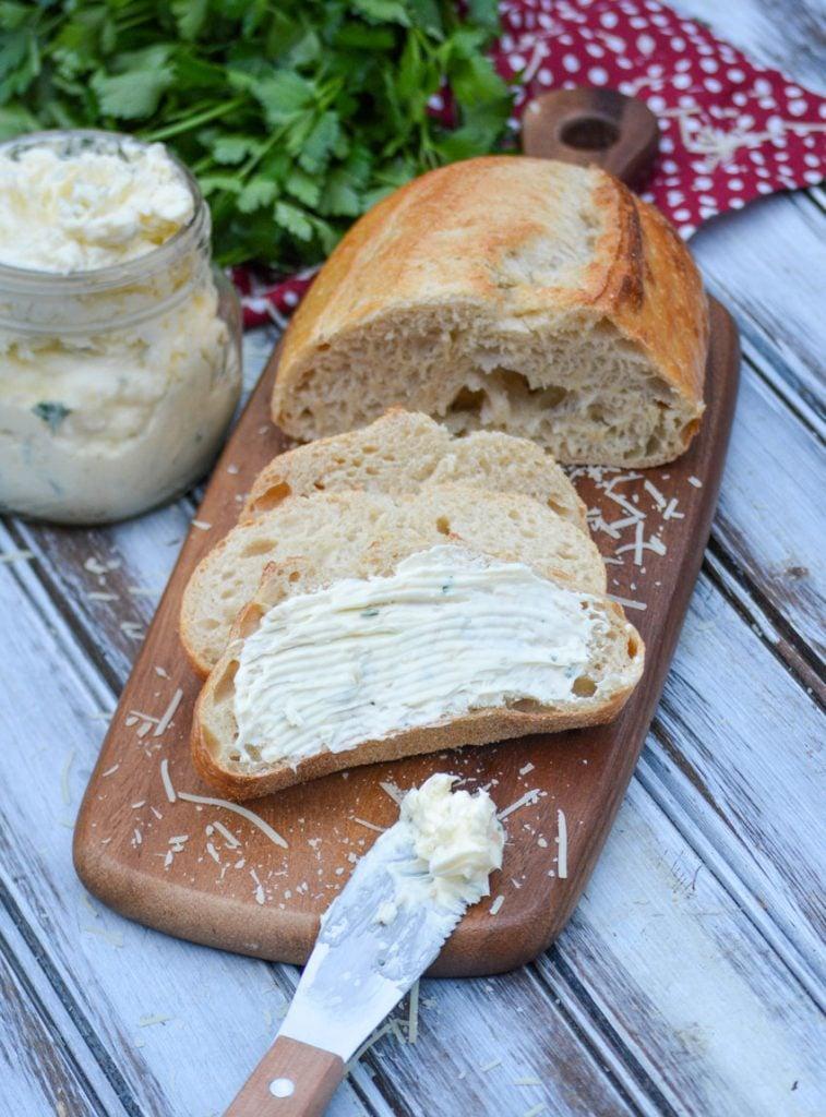 Italian garlic infused butter spread over sliced Italian bread on a wooden cutting board