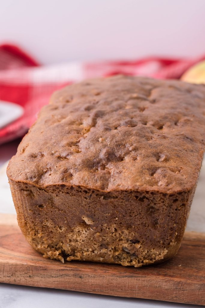 a brown loaf of apple walnut bread shown on a wooden cutting board