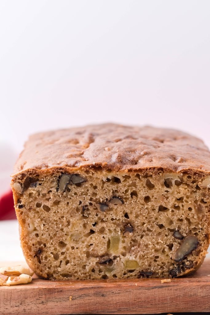 a loaf of apple walnut bread shown sliced open to reveal the soft inside with tender apples and walnuts