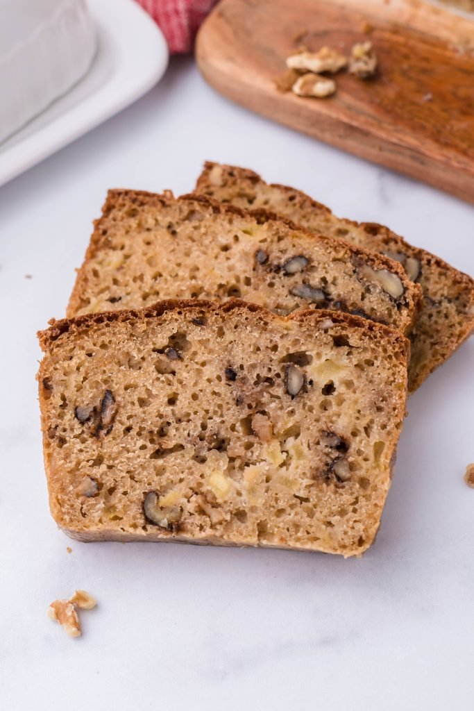 three slices of apple walnut bread fanned out on a white marble counter top