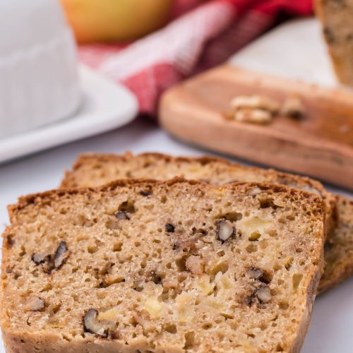 slices of fresh apple walnut bread shown on a white background