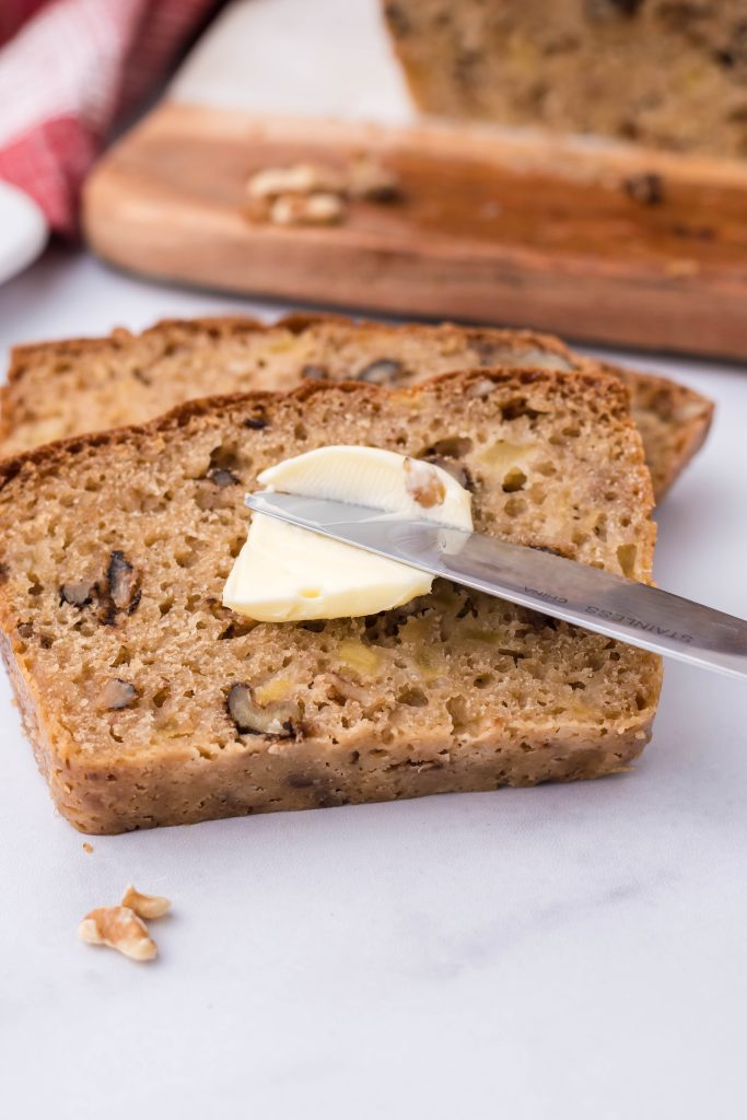 soft butter being spread on a fresh slice of apple walnut bread