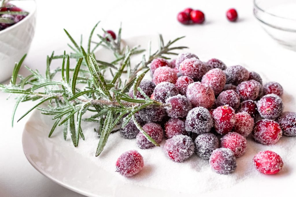 sugared cranberries and rosemary shown on a bed of white sugar