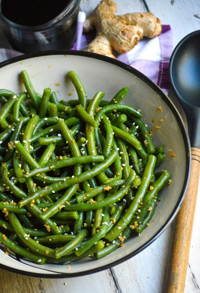 garlic ginger green beans served in a ceramic bowl with a wooden spoon, ginger root, and soy sauce in the background