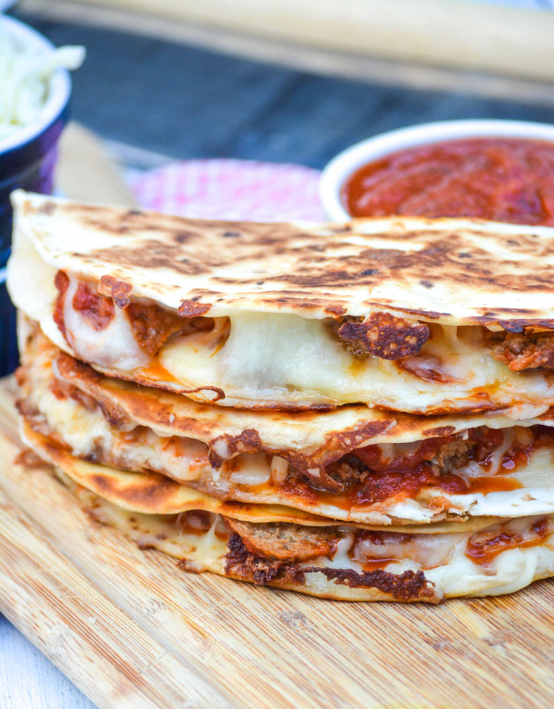 a stack of meatball quesadillas on a wooden cutting board