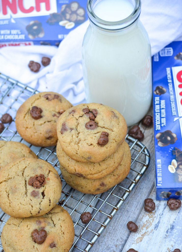 a stack of nestle buncha crunch cookies in front of a glass of milk