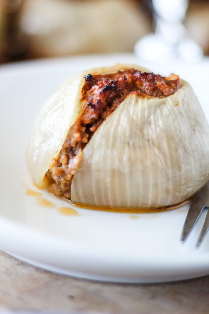 a grilled onion bomb served on a white plate