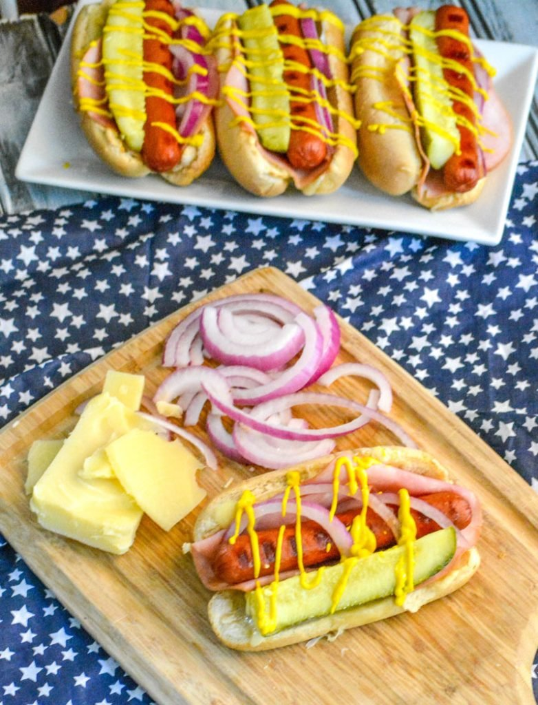 Hot Dogs with swiss cheese, dill pickle, red onion, and yellow mustard