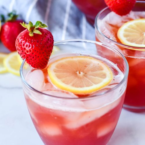 sweet strawberry iced tea served with sliced lemon and fresh strawberry for garnish