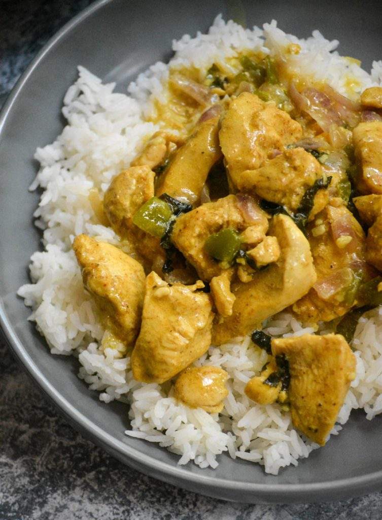 Basil Chicken in Coconut Curry Sauce spread over a bed of steamed white rice in a gray bowl