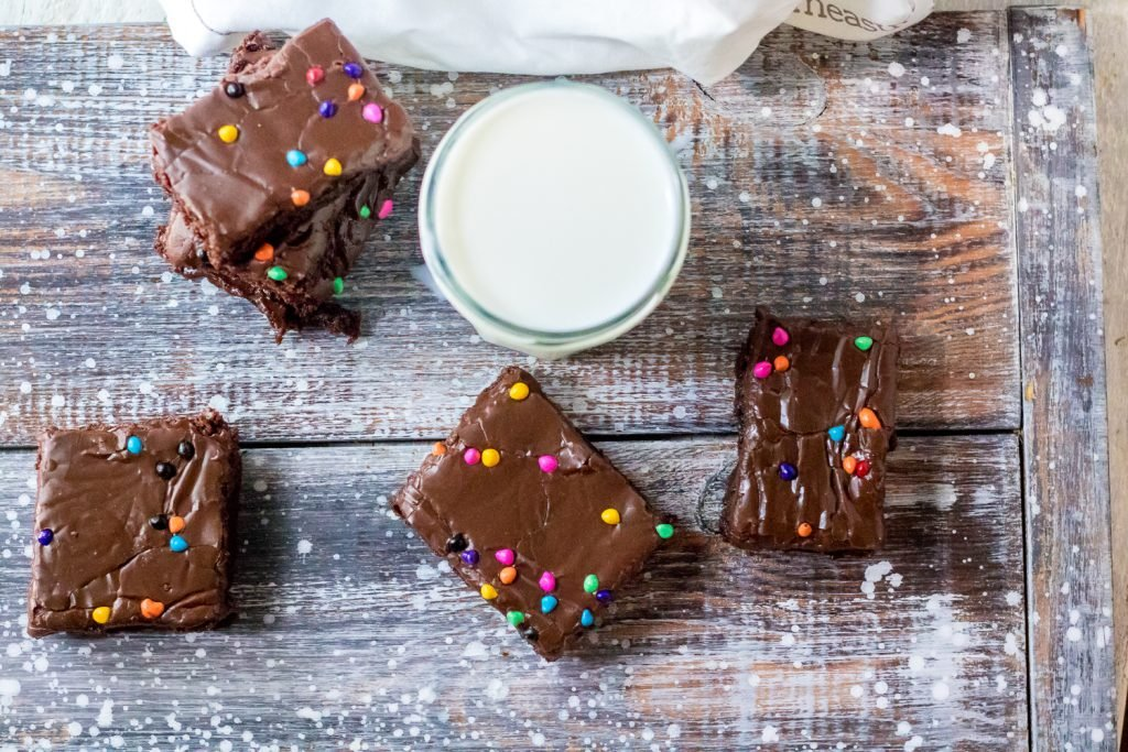 cosmic brownies on a weathered wooden back drop shown with a full glass of milk