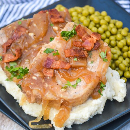 two smothered pork chops served over mashed potatoes with peas on the side on a black square plate