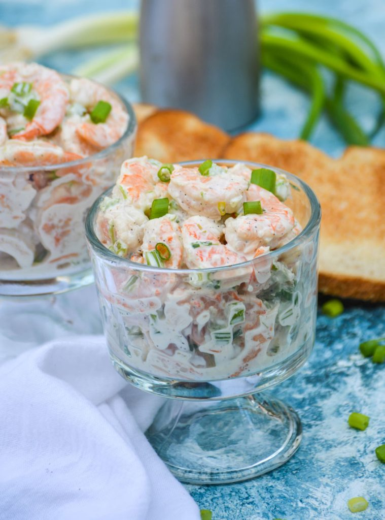 creamy shrimp salad topped with thinly sliced scallions and shown in a glass bowl on a blue backdrop with a white cloth napkin and slices of toast in the background