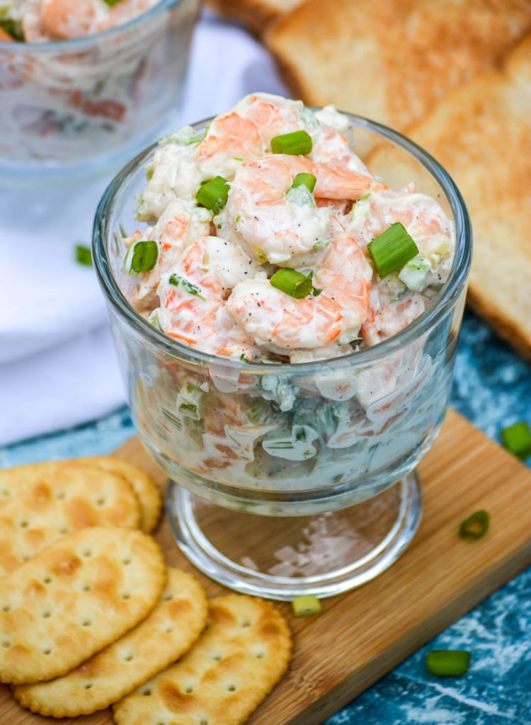 creamy shrimp salad topped with thinly sliced scallions and shown in a glass bowl set on a narrow wooden cutting board with crackers, a white cloth napkin, and slices of toast in the background