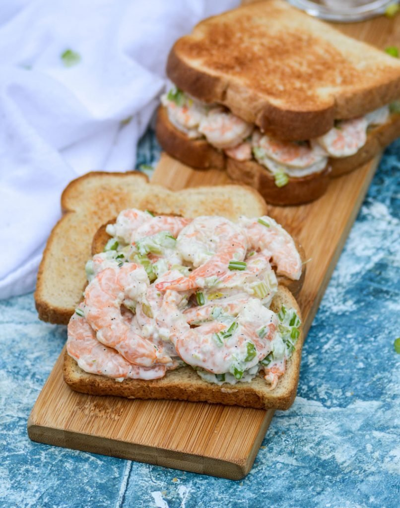 creamy shrimp salad shown on toasted bread being made into sandwiches a top a wooden cutting board