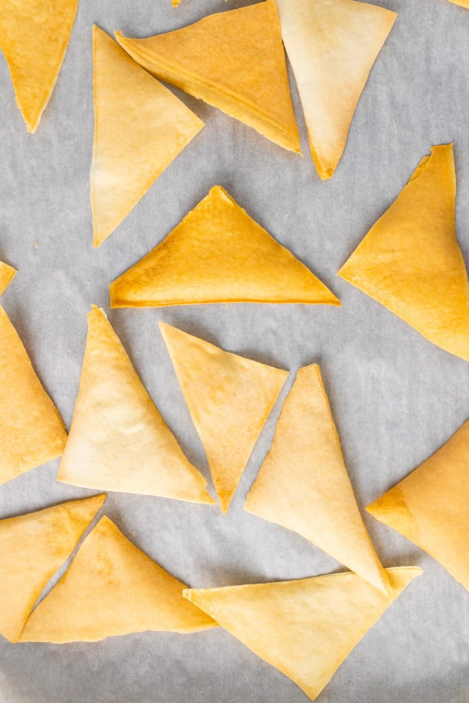 golden brown crispy baked wonton chips on a piece of parchment paper