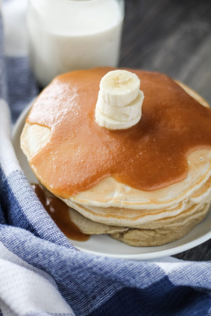 a stack of banana pancakes with peanut butter syrup shown on a white plate with a glass of milk in the background