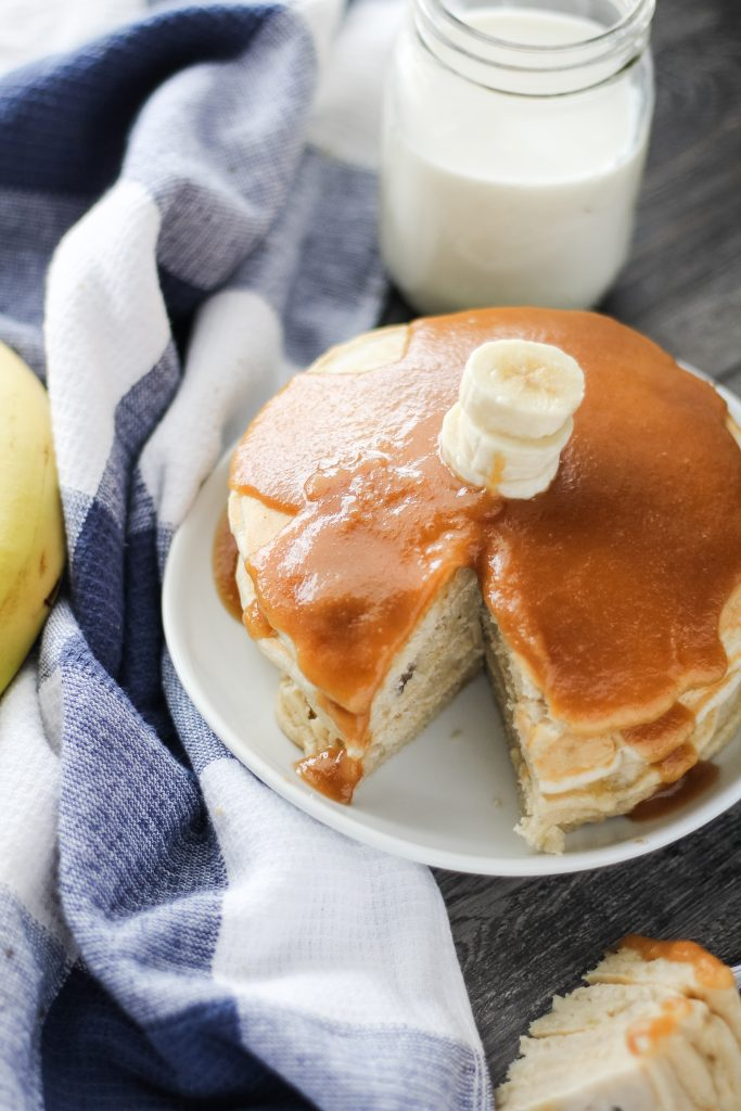 a stack of banana pancakes with peanut butter syrup shown on a white plate with a slice removed