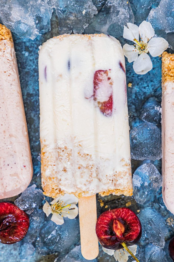 cherry cheesecake popsicles laid out over ice cubes