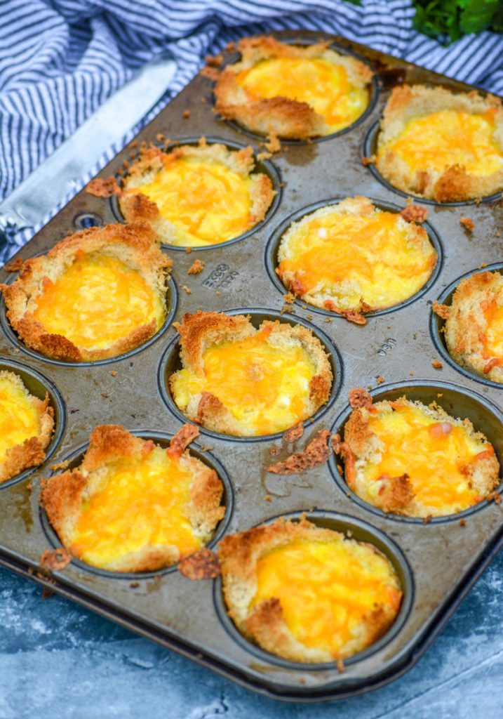 Ham, Egg, & Cheese Toast Cups in the silver muffin tin they were cooked in on a blue background with a striped cloth napkin