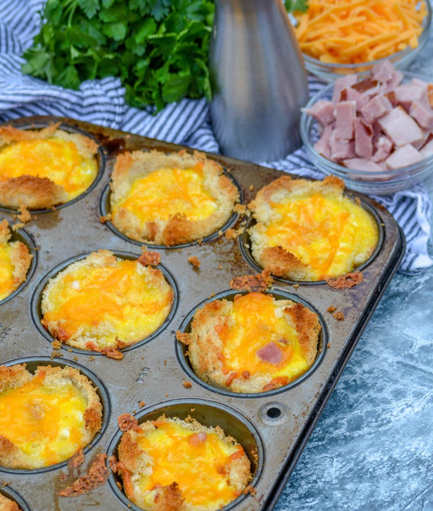 Ham, Egg, & Cheese Toast Cups in the silver muffin tin they were cooked in- shredded cheese, chopped ham, and fresh herbs in the background