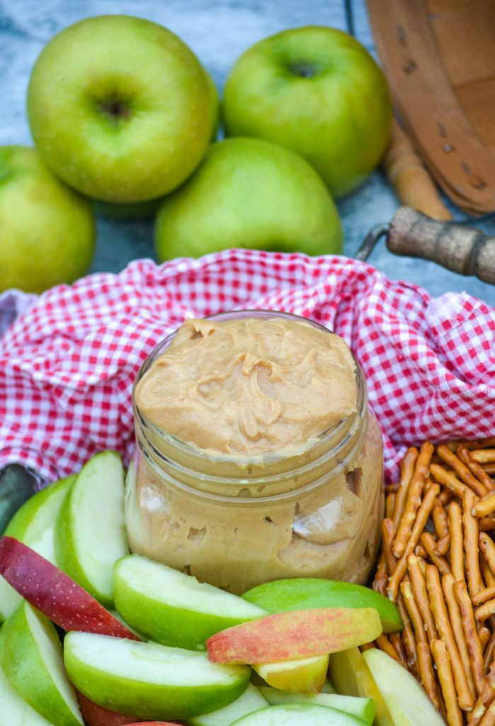 creamy peanut butter apple dip in a small mason jar on a metal serving tray with apples & pretzels with a red & white checkered cloth napkin in the background