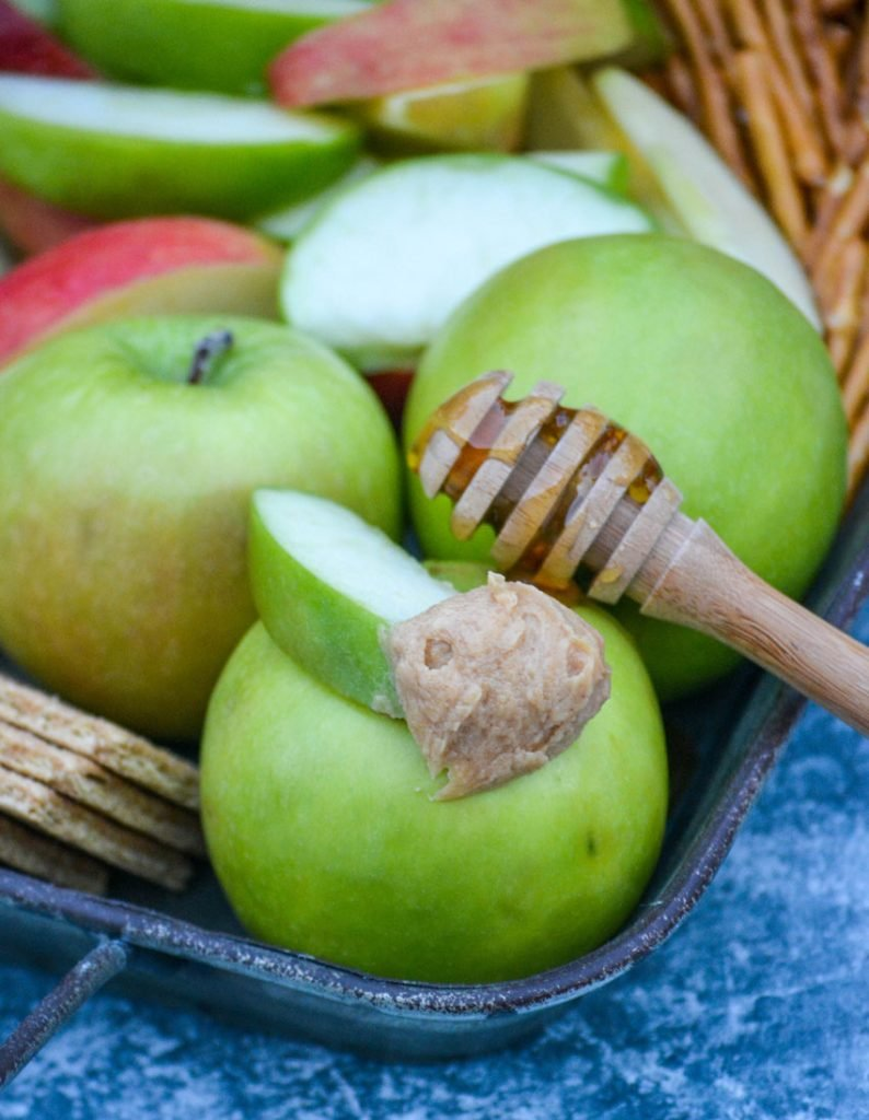 a scoop of healthy peanut butter apple dip shown on a green apple slice resting on top of a whole green apple with a honey covered wooden dipper behind it
