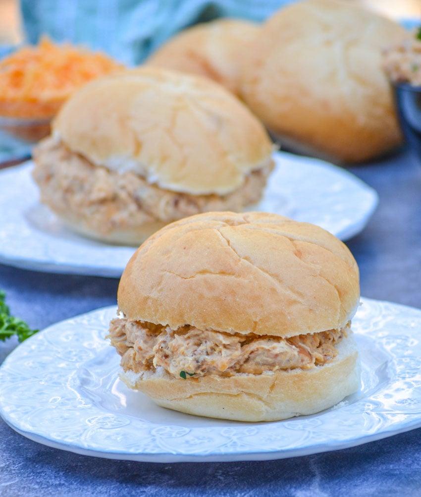 crockpot crack chicken sandwiches shown on white circular plates