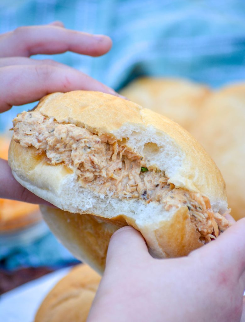 small hands holding up a crockpot crack chicken sandwich with a bite taken out of the center to show the creamy meat & cheese mixture inside