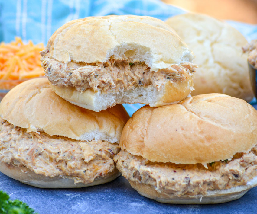 a crockpot crack chicken sandwich shown with a bite taken out of it and sitting on top of two other prepared crack chicken sandwiches