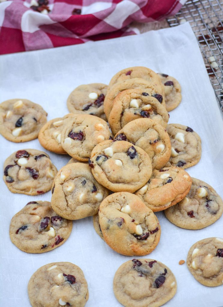 white chocolate chip & cranberry cookies piled high on a sheet of white parchment paper