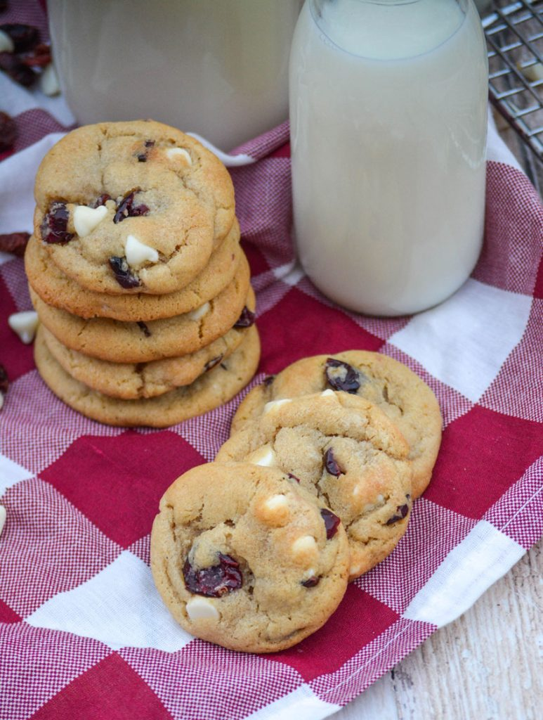 a stack of chewy white chocolate chip & cranberry cookies beside a glass of cold milk