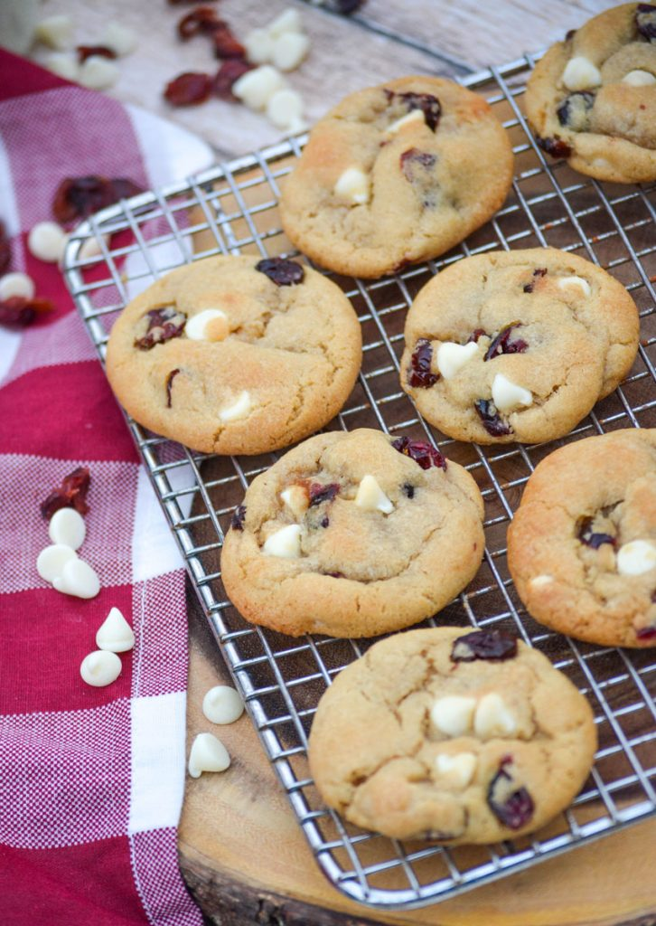 cranberry white chocolate chip cookies shown on a wire rack on top of a red and white plaid cloth napkin