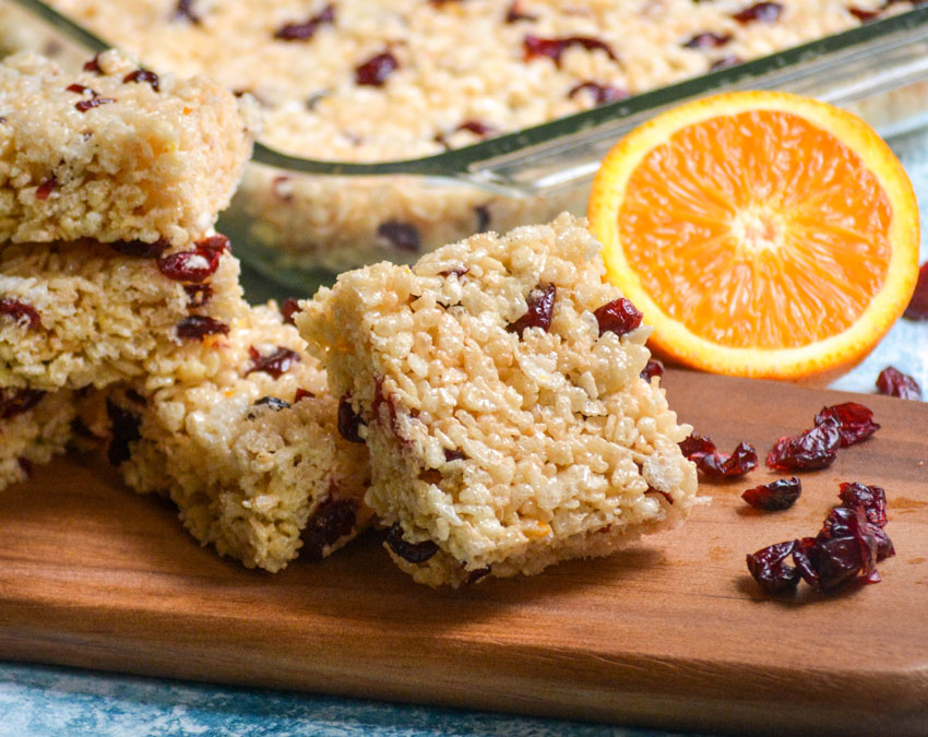 cranberry orange rice krispie treats squares served on a wooden cutting board