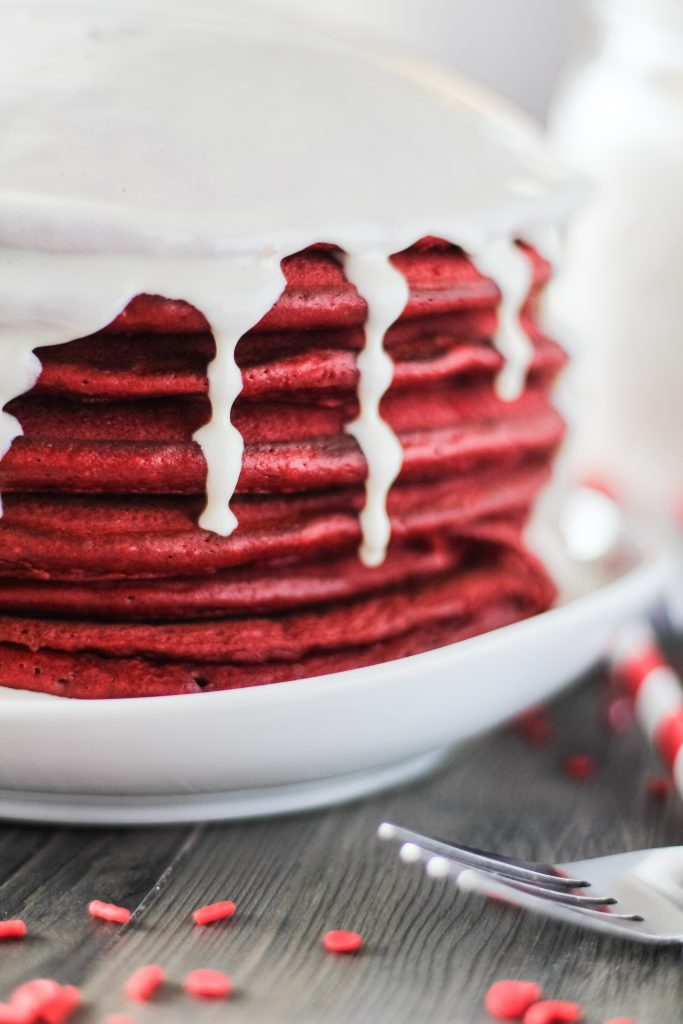 a stack of red velvet pancakes with cream cheese glaze on a white plate