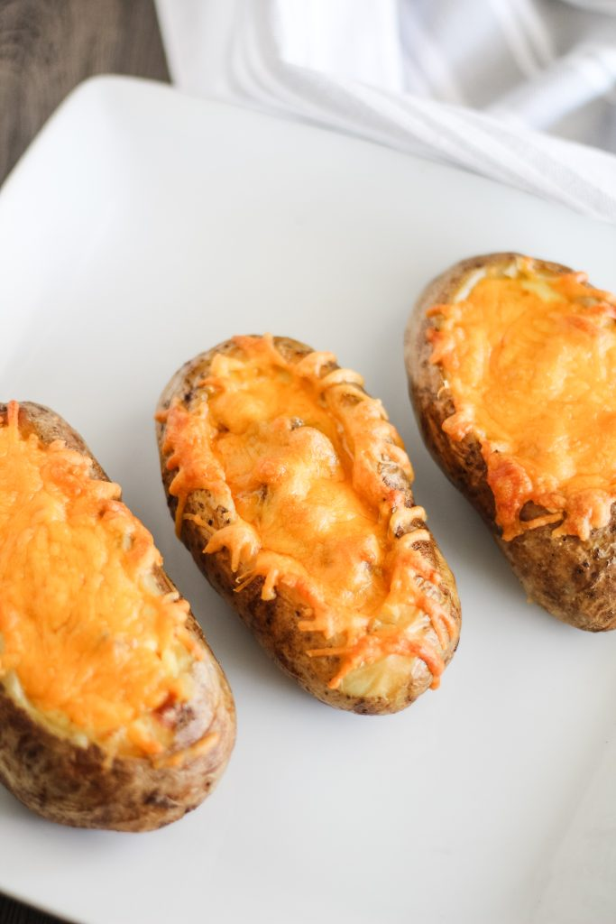three twice baked breakfast potatoes lined up on a white plate