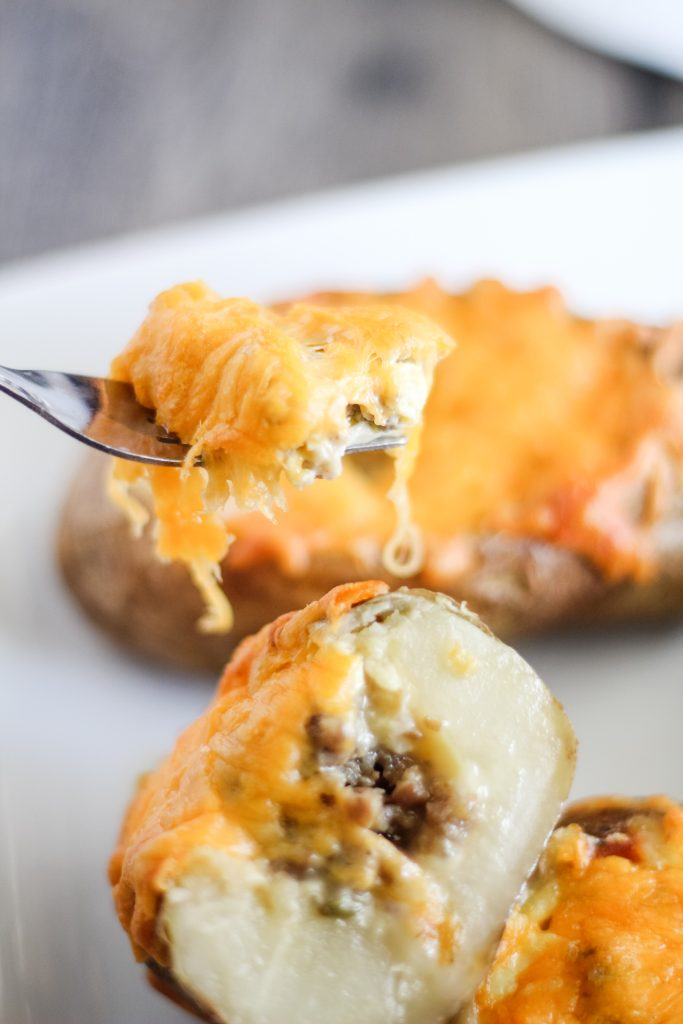 a fork shown lifting a cheesy bite out of a twice baked potato