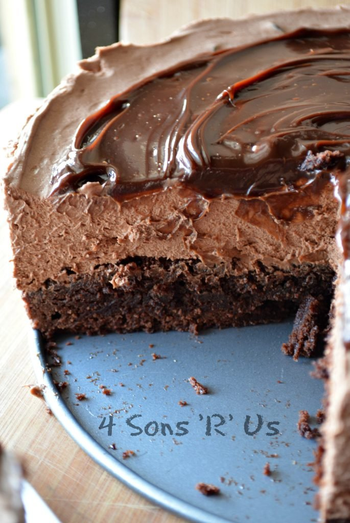 No Bake, Hot Fudge Chocolate Cheesecake on a brown back ground with a slice removed to reveal the inside layers
