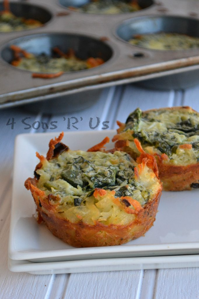 two Spinach & Herbed Goat Cheese Hashbrown Nests sitting on top of two stacked white square plates with a silver muffin tin full of nests in the background