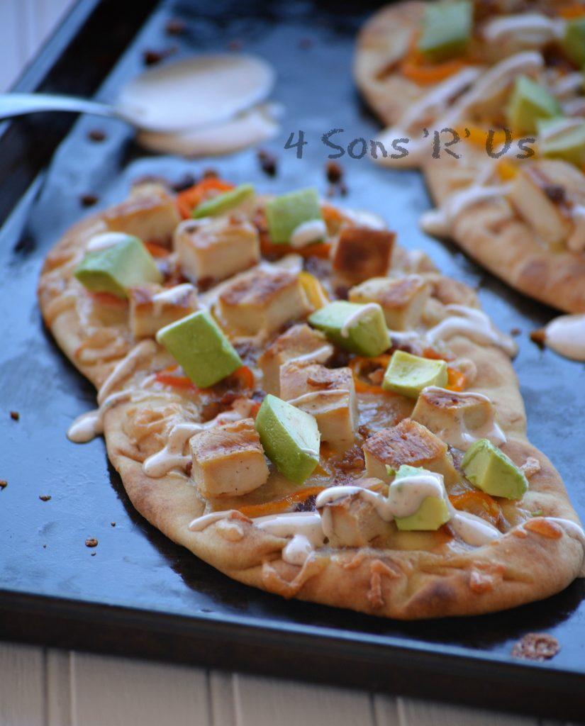 naan bread on a sheet pan has been topped with chunks of cooked chicken, avocados, and sweet pepper rings with a chipotle ranch drizzle. A spoon with chipotle ranch is seen in the background.