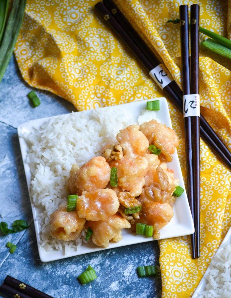 crispy honey walnut shrimp served alongside steamed white rice on a small white plate