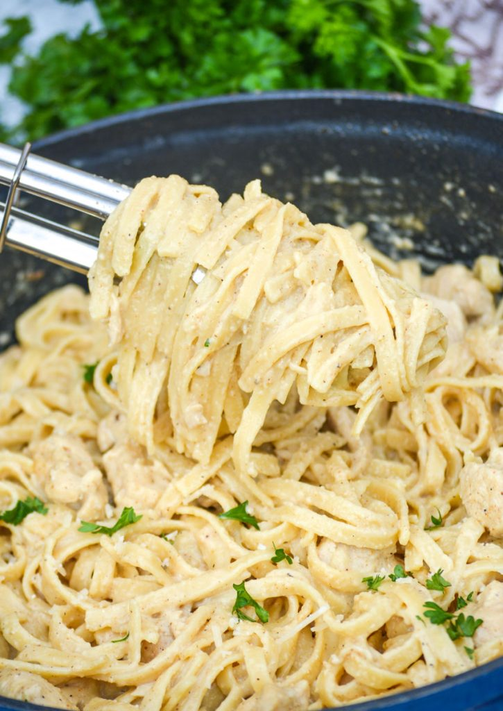 one pot Cajun chicken alfredo pasta in a large blue cast iron enameled dutch oven