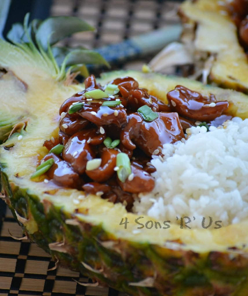 Chicken Teriyaki Pineapple Boats shows saucey, teriyaki glazed chicken pieces served next to tender white rice in a halved, hollowed out pineapple bowl