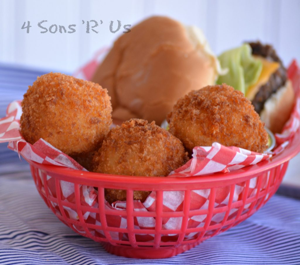 Giant Cheesy Tater Tots in a paper lined lunch basket with a hamburger