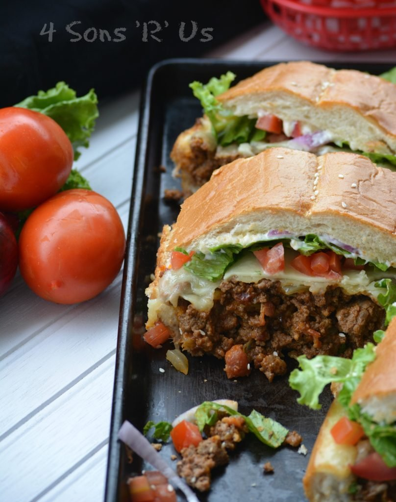 Bacon Cheeseburger Stuffed French Bread shown slice into sandwiches on a dark baking sheet