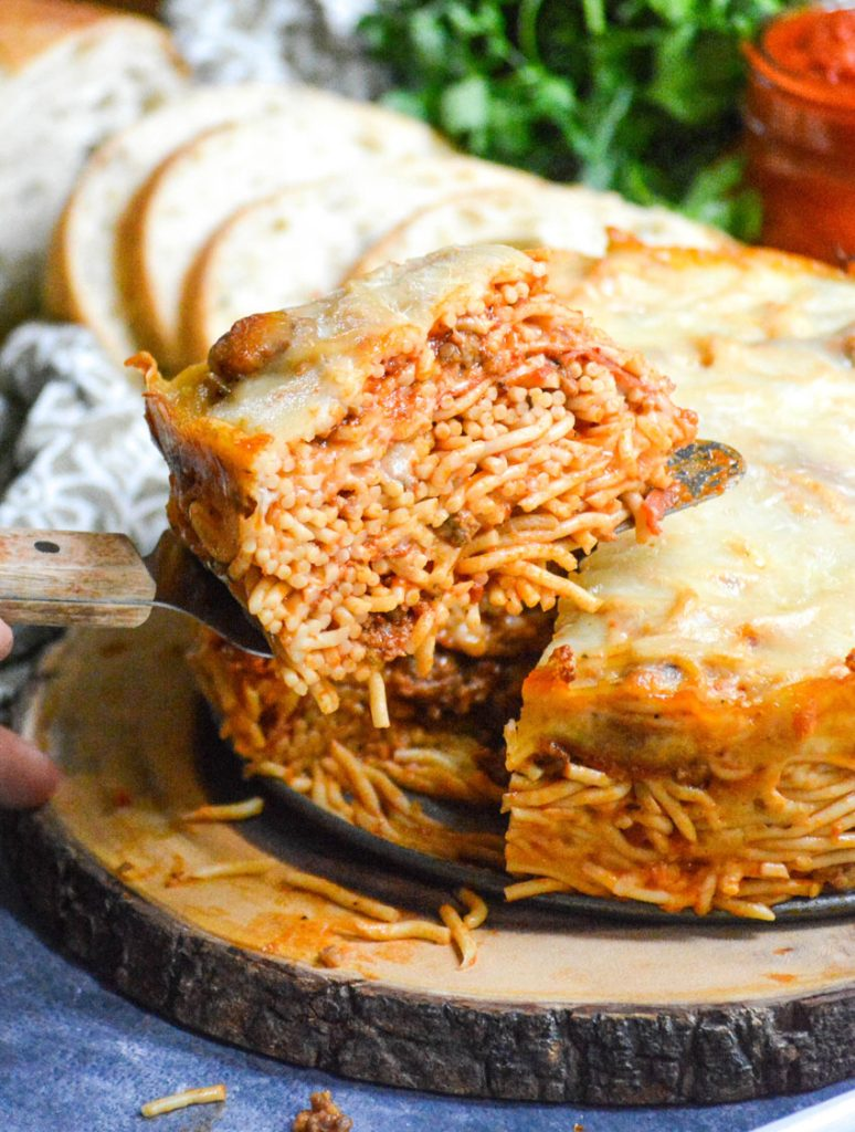 baked spaghetti pie served on a wooden cutting board